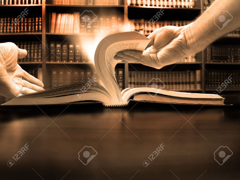 27275235-Hands-turning-pages-in-old-book-with-library-in-background-Stock-Photo